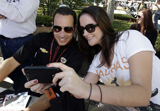 "Daphne Franco takes a ""selfie"" with Helio Castroneves during an autograph session for fans."