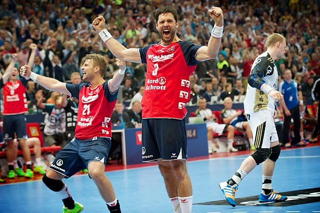 Tobia Karlsson (3) and Jacob Heinl (21) from Flesnburg-Handewitt celebrate their Champions League Final win as Rene Toft Hansen (7) from THW Kiel walks away dejectedly.