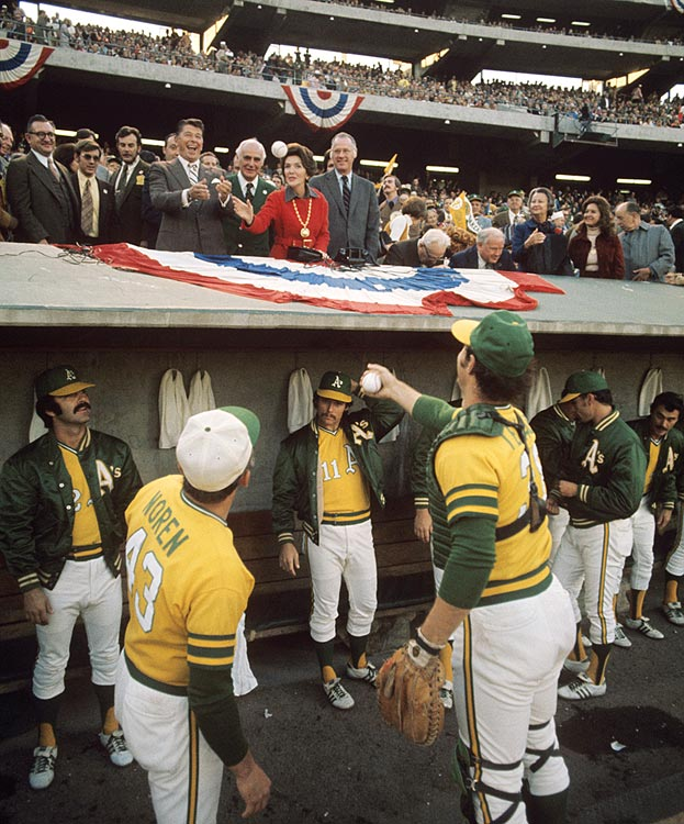 Oakland A's catcher Gene Tenace tosses a ball to California Governor Ronald Reagan during Game 3 of the World Series between the Athletics and the Cincinnati Reds at Oakland-Alameda County Coliseum.