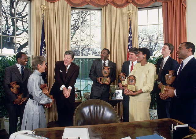 President Reagan gets some golf tips from golfer Patty Sheehan while Sports Illustrated 1987 Sportsmen and Sportswomen of the Year (left to right) Ethiopia runner Kip Keino, Chicago Bulls point guard Rory Sparrow, Wake Forest fullback Chip Rives, Athletics West hurdler Judi Brown King, Atlanta Braves outfielder Dale Murphy, and Cincinnati Bengals linebacker Reggie Williams look on during a visit to the White House.
