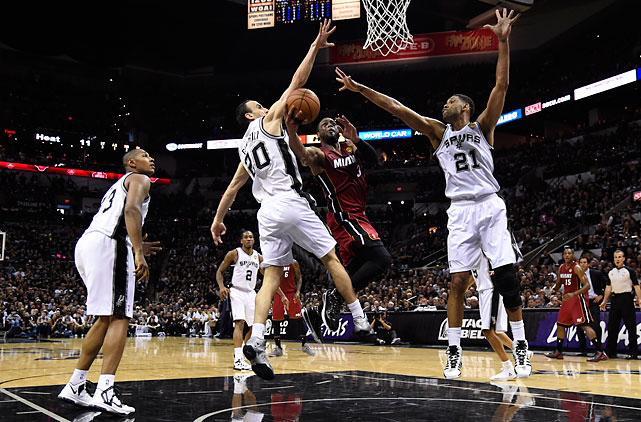 Manu Ginobili (left) and Tim Duncan defend Dwyane Wade, who finished with 19 points for the Heat.