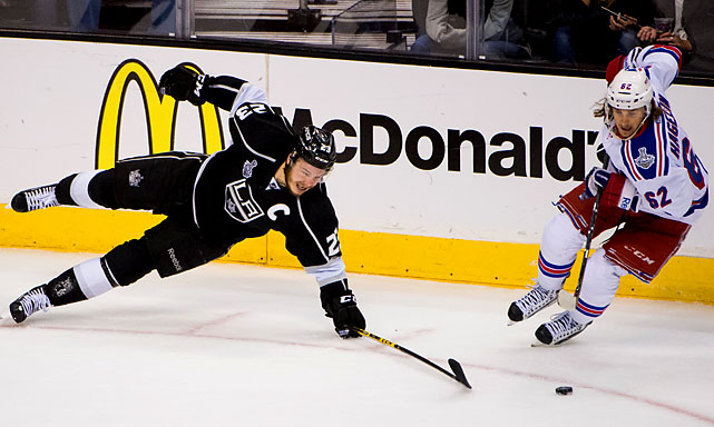 Dustin Brown of the Kings battles Carl Hagelin for the puck.