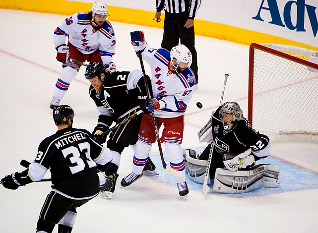 Jonathan Quick attempts a save with Benoit Pouliot of the New York Rangers and Matt Greene of the Kings battling in front of the net.
