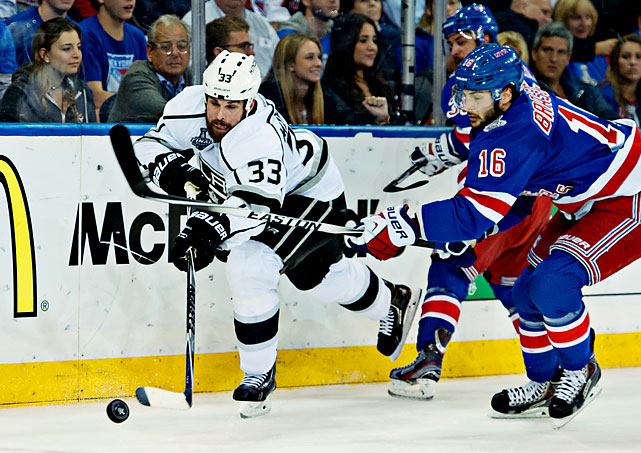 WIllie Mitchell of the Kings and Derick Brassard of the Rangers go at it.