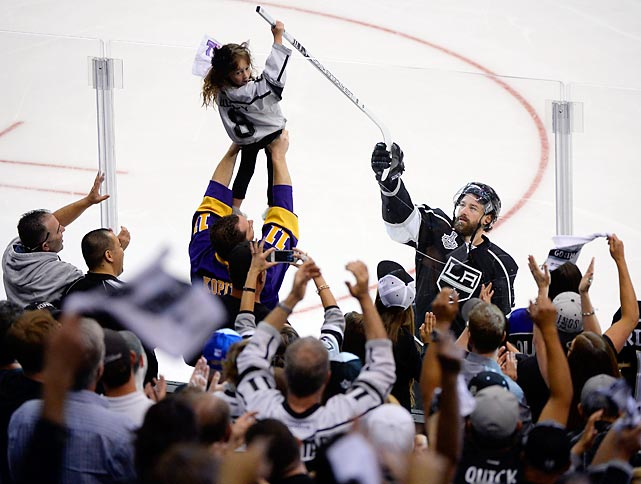 Justin Williams of the Los Angeles Kings hands his stick to a young fan after scoring the overtime game-winner against the New York Rangers. The Kings won Game 1, 3-2 at home.