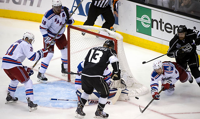 Anton Stralman of the New York Rangers dives for the puck as Kyle Clifford and Trevor Lewis look on.