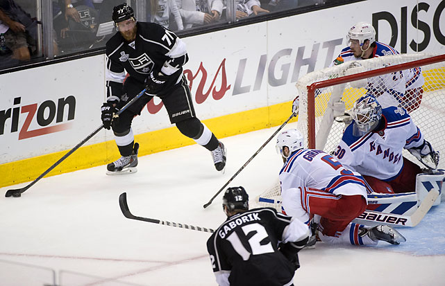 Jordan Nolan of the Kings skates with the puck as Dan Girardi, Ryan McDonagh and Henrik Lundqvist defend.