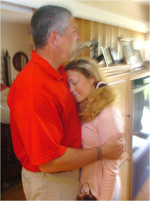 Michael Dowd holds his wife in their Florida apartment, savoring every moment together.