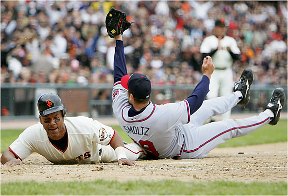 Giants veteran Moises Alou scores on a wild pitch from Atlanta's John Smoltz.