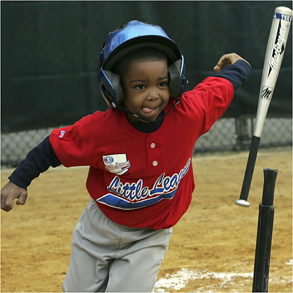 A Little Leaguer tosses his bat aside and dashes off toward first base.