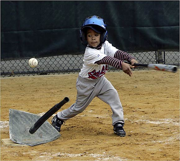 A young batter hits off a tee during Little League Opening Day in New York City.