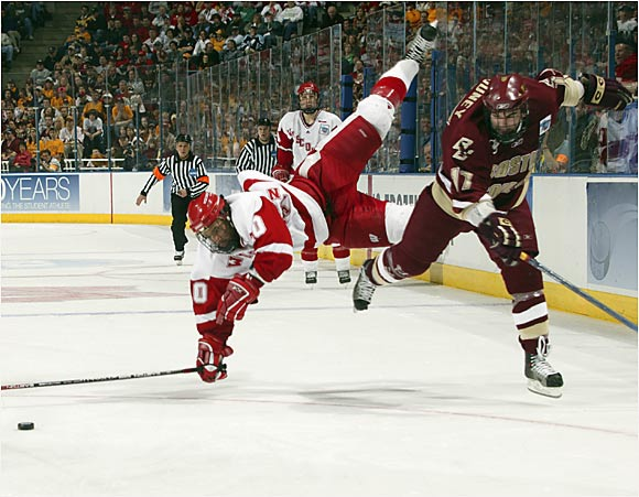 Junior forward Robbie Earl (left) collides with Eagles forward Joe Rooney during the Frozen Four championship game in Milwaukee.