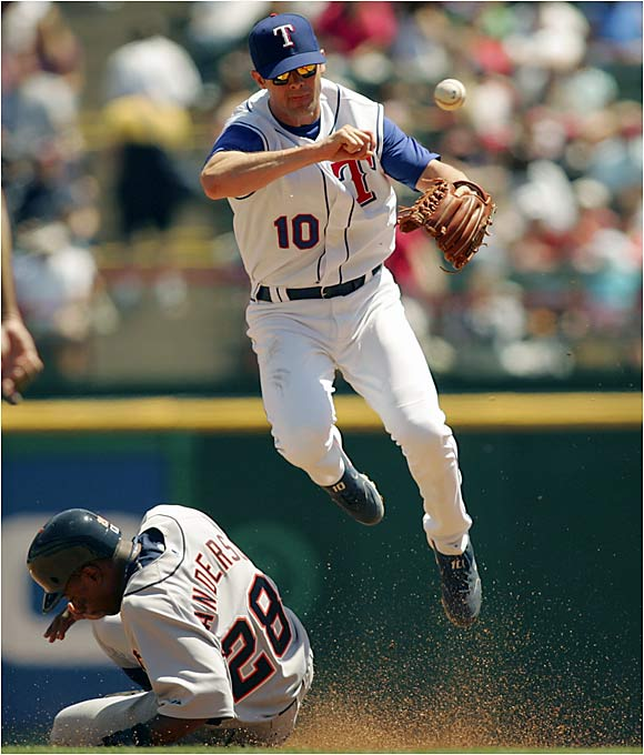Michael Young attempts to turn the double play against the Tigers in Texas.