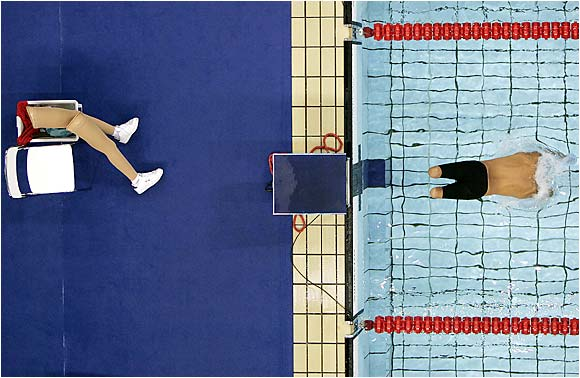Xavier Torres of Spain leaves his prosthetics in the clothing basket as he dives in at the start of a 200-meter freestyle heat at the Paralympic Games in Athens.