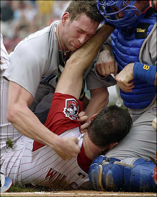 Reds starter Paul Wilson was trying to bunt when Cubs reliever Kyle Farnsworth threw a fastball high and tight. Wilson said something to Farnsworth, who charged toward home plate, flipped off his glove and slammed Wilson to the ground before landing a punch to the face. A pileup quickly ensued on top of the two pitchers.