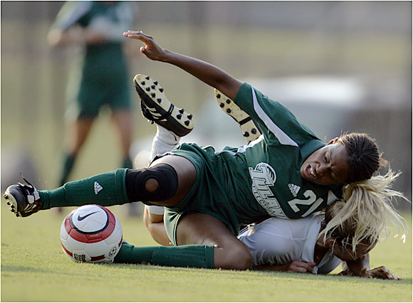 Tulane's Keisha Kennedy keeps her focus on the ball after getting taken down by a Louisville defender.