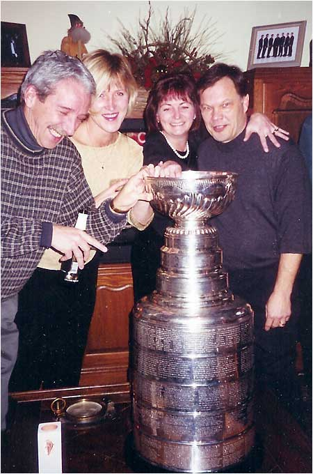 "This photo was taken at a 2002 Christmas party at a friend's house in Troy, Mich. His sister-in-law was employed by Marian Illitch and arranged to have the ""Blessed Cup"" sent to the house as a surprise (OH YEAH!!!!).  In the picture (l-r): Mark Dembowski, Bobbie Dembowski, Rosie Jokinen, and Denny Jokinen (No relation to Olli or Jussi).  I actually was allowed to hold the cup Stevie Yzerman style over the head as it made its royal entrance. My wife's comment was ""This is really exciting for you isn't it?"" My reply ""Better than sex ... right now."" -- Mark Dembowski"