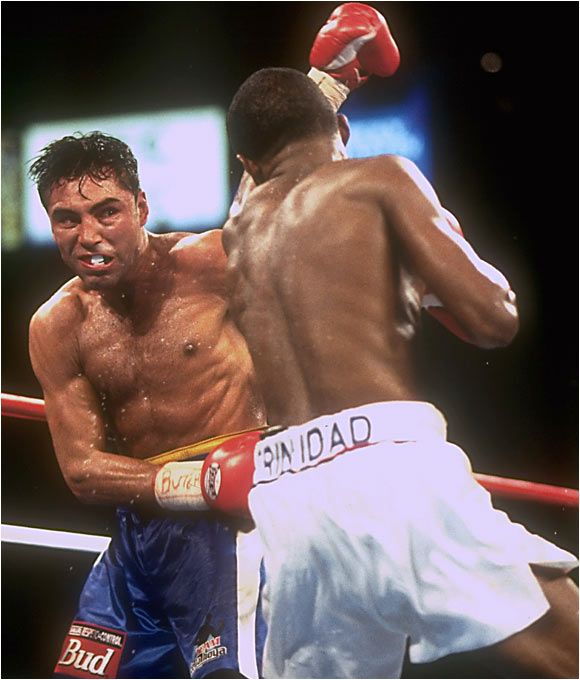 "Forget the Odd Couple jokes. Oscar and Felix was a match fight fans had been dreaming about. This showdown between two undefeated welterweight champions featured the straight-ahead power of Puerto Rican national hero Trinidad (whose record of 35-0-0 included 30 KOs) against the mobility and boxing skill of De La Hoya. For most of the bout, Oscar put on a dazzling display, circling, jabbing and completely neutralizing Trinidad's attack. But in the closing rounds, believing he ""had it won,"" De La Hoya went on the defensive and coasted to the final bell. It cost him, as the judges gave Trinidad a majority decision."