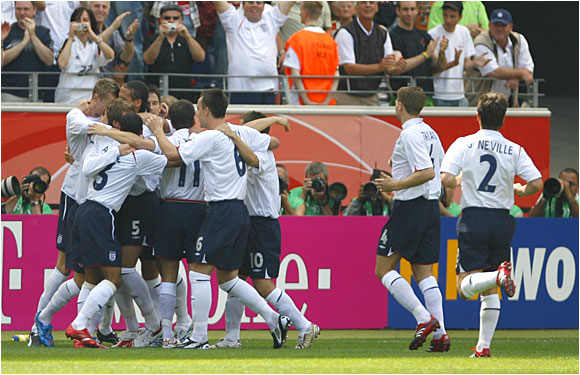England celebrates after David Beckham's free kick was ricocheted into the goal by Paraguay in the third minute.