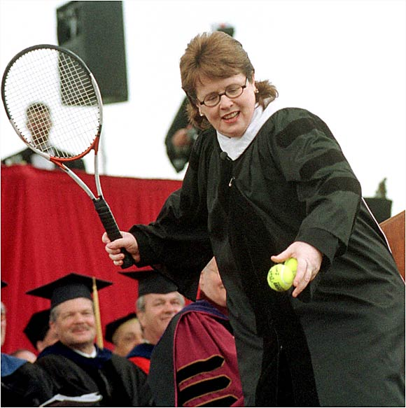 Billie Jean King lobs some autographed tennis balls into the sea of graduates before her speech at UMass in 2000.