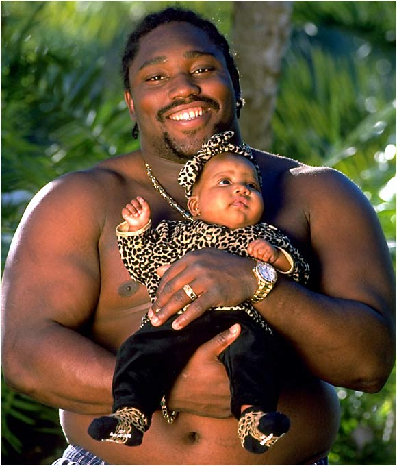 "Warren Sapp, all 278 pounds of him, holds tight to his football-sized daughter, Mercedes, in this February 1998 picture. Sapp's wife, JaMiko, spoke to SI about her husband: ""There is a side that people don't see. He can be gentle and caring."""