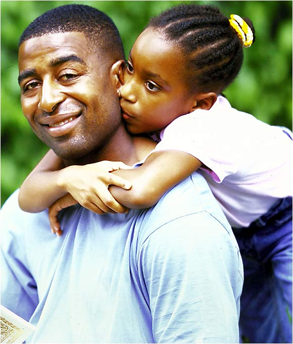 Cris Carter unleashes a huge smile as his five-year-old daughter, Monterae, gives him a hug in this photo from May 2000.