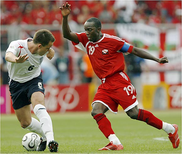 Trinidad and Tobago's Dwight Yorke (right) spins around defenseman John Terry during Thursday's match in Nuremberg that saw England score two late goals for its second victory.