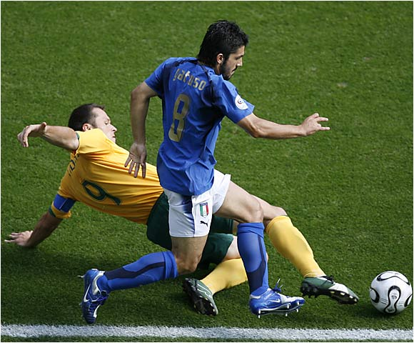 Australia's Mark Viduka dives ahead of Italy's Gennaro Gattuso to gain possession during Italy's 1-0 victory over Australia.