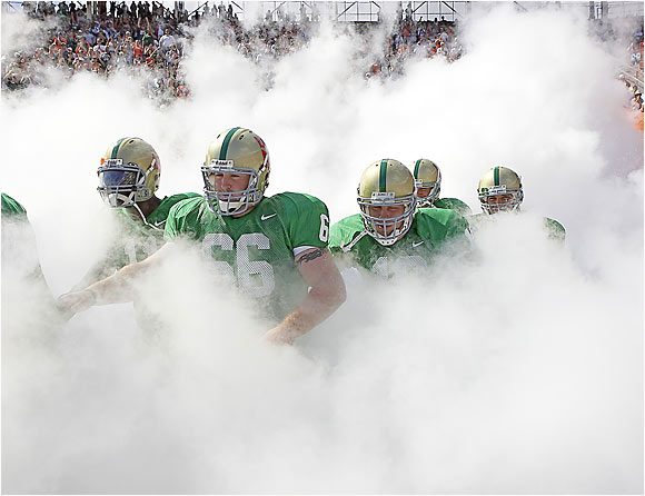 Wearing new uniforms, University of Miami players emerge from a manmade fog on Oct. 29, 2005, to play their first game in the Orange Bowl less than a week after Hurricane Wilma swept through South Florida. The 'Canes defeated North Carolina 34-16.
