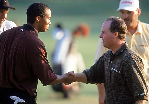 Woods shakes hands with Bob May, whom Tiger defeated in a playoff. The two were neck and neck for much of the final day before Tiger won his third consecutive major.