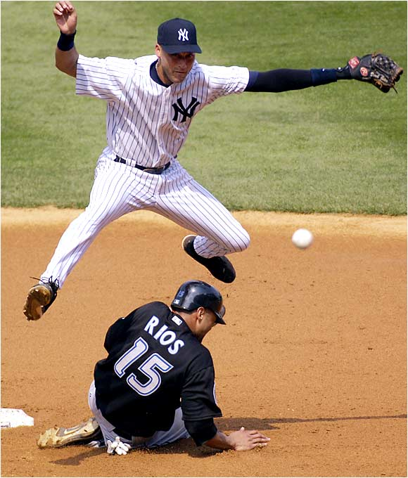 Shortstop Derek Jeter turns a double play with a throw to first as he leaps over a sliding Alex Rios in the sixth inning of the Yankees' 8-1 win over the Blue Jays on Aug. 3.