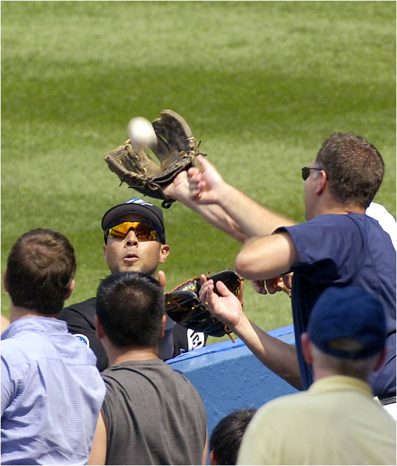 A fan extends his glove to prevent Blue Jays right fielder Alex Rios from catching a foul ball at Yankee Stadium on Aug. 3 during the Yankees' third consecutive win over the Jays.