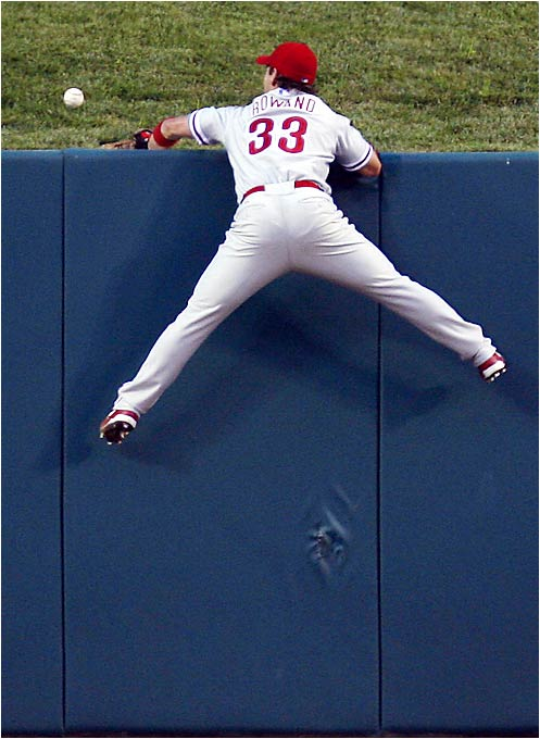Phillies center fielder Aaron Rowand climbs the wall but fails to reach a home run ball hit by Chris Duncan, which scored two for the Cardinals in the second inning on Aug. 2. Rowand would later respond with a solo shot in the fifth as the Phillies routed the Cardinals 16-8.