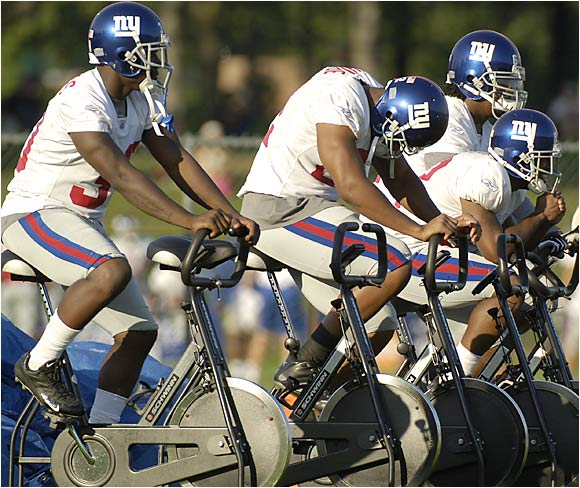 After seeing Jeremy Shockey get lit up by teammate Will Demps, numerous Giants display their fear of being on the rude end of a highlight reel. Although simply riding stationary bikes, the G-Men wear their protective head gear because one never knows when Big Blue head man Tom Coughlin might toss them onto the practice field.