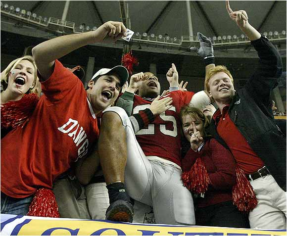 Michael Johnson (No. 25) celebrated in the stands with fans after Georgia defeated the University of Arkansas in the 2003 SEC Championship game.