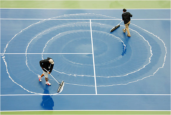Attendants squeegee water off the court in Arthur Ashe Stadium during a rain delay Monday at the U.S. Open.