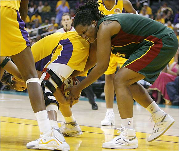 The Los Angeles Sparks' Christi Thomas, left, and the Seattle Storm's Tiffani Johnson are bored with basketball and decide to break out a football game.