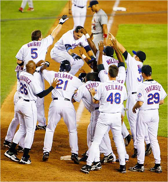 The Mets' Carlos Beltran leaps to home plate as teammates celebrate his game-winning two-run homer in the ninth against the Cardinals on Aug 22. The Mets swept the Central Division-leading Cards in three games at Shea.