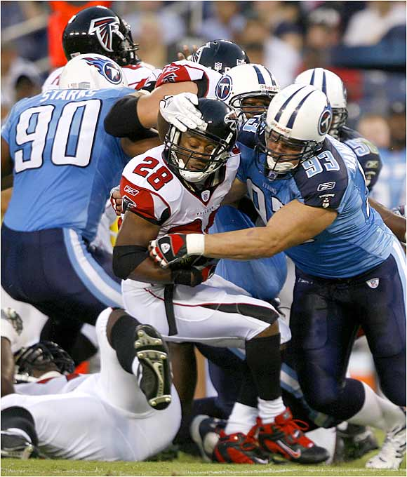 Warrick Dunn (28) of the Falcons is stopped by the Titans' Kyle Vanden Bosch. Atlanta won 20-6.