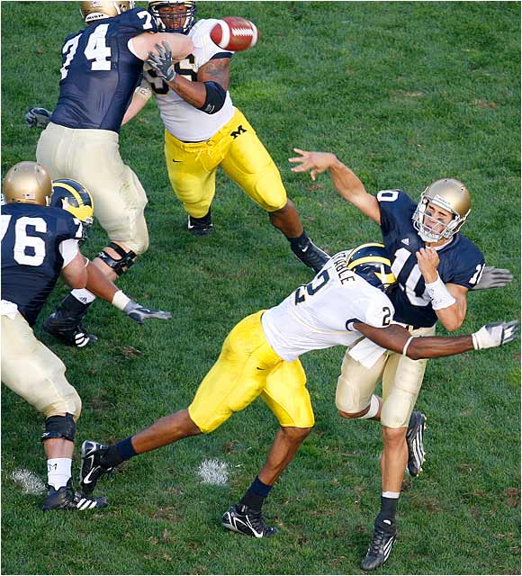 Shawn Crable (2) of Michigan clobbers Brady Quinn as Quinn releases a pass. Quinn's Heisman chances took a big hit on Saturday.