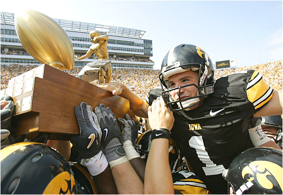 Kyle Schlicher, who iced the win with a 44-yard field goal with 42 seconds left, and the Hawkeyes celebrate with the Cy-Hawk Trophy.