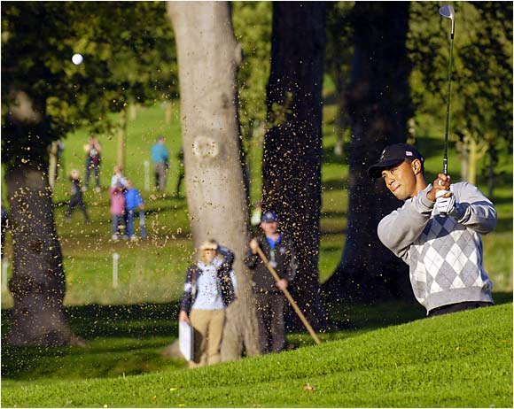 Tiger Woods plays from a bunker on the 4th hole during his morning four-ball match.