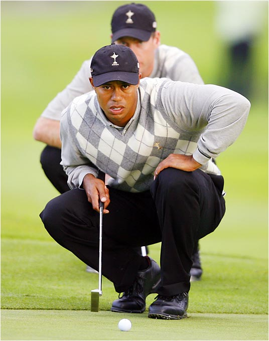 Tiger Woods lines up a putt with teammate Jim Furyk behind him during their afternoon foursome against Sergio Garcia and Luke Donald. Woods and Furyk won their morning four-ball match but fell short in the afternoon.