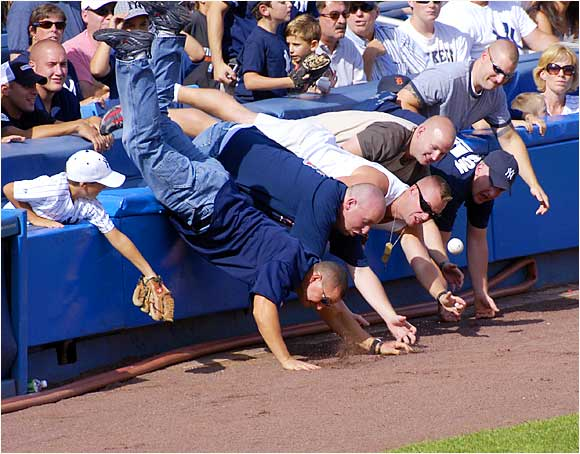 Fans reach over the rail along the third base line in a failed attempt to grab a foul ball during the game between the Yankees and Tigers at Yankee Stadium on Aug. 31.
