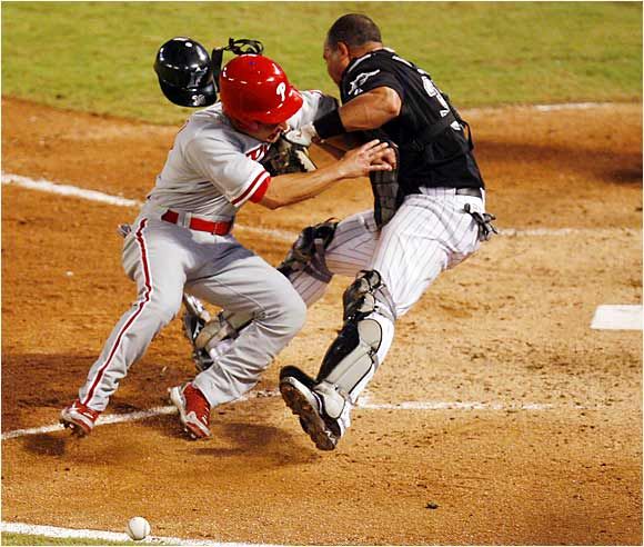 The Phillies' Shane Victorino bowls over Marlins catcher Miguel Olivo to tie the score off a single by Jeff Conine in the ninth inning. The Marlins won 4-3 with a Cody Ross RBI single in the 10th.
