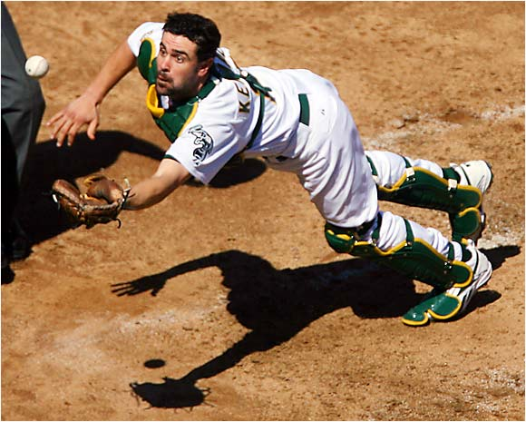 A's catcher Jason Kendall dives to catch a bunt pop-out by the White Sox' Tadahito Iguchi in the third inning of a 7-4 Oakland win on Saturday. The Athletics swept their three-game series with Chicago to expand their lead in the AL West to seven games.