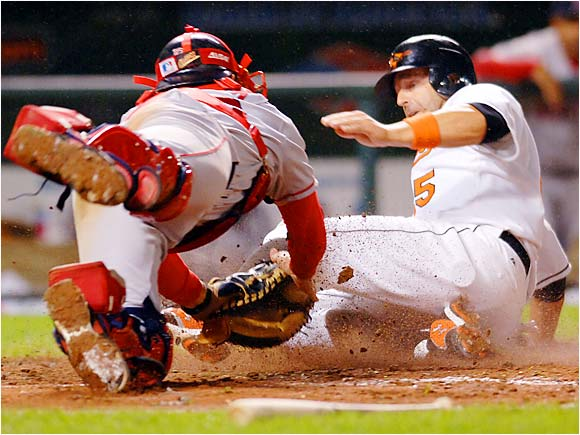 The Orioles' Kevin Millar beats the diving tag by Jason Varitek to score on a single by Jeff Fiorentino in the fourth inning on Sept. 14. Varitek's return earlier in the month has done little to help the ailing Red Sox come close to earning a playoff berth.