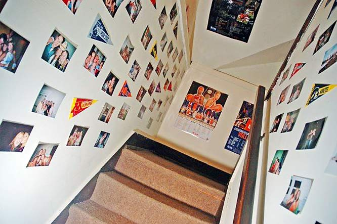 Pictures, posters and banners line the stairway. The house has two stairways that run side by side, which were originally intended to separate servants from the family who owned the home.