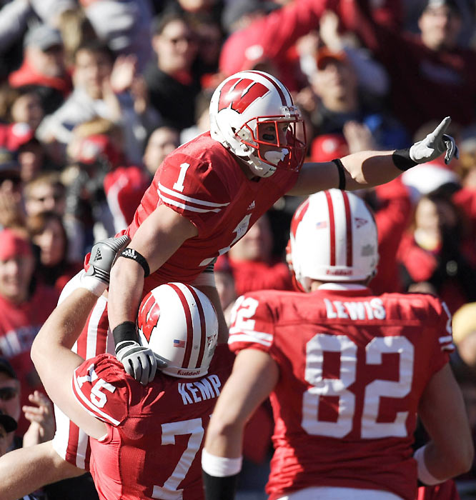 Offensive lineman Andy Kemp (76) hoists teammate Luke Swan after the Wisconsin wide receiver caught a third-quarter touchdown pass in the Badgers' come-from-behind win over Illinois.