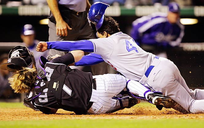 The Dodgers' Delwyn Young collides with Rockies catcher J.D. Closser; Young was called out on the play in the seventh inning on Sept. 27.  The Dodgers won 6-4, and scored 36 runs over three games at Coors Field to sweep their series with the Rockies.